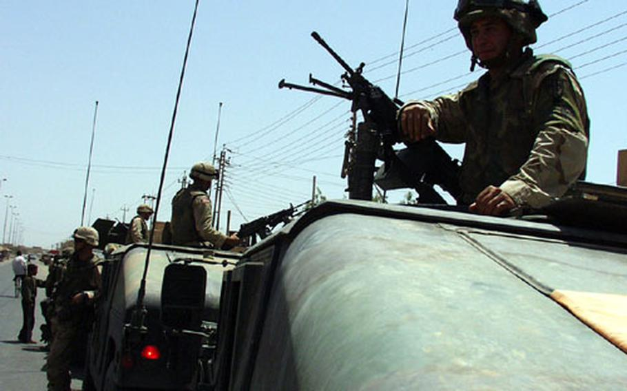 Pfc. Joseph Lisciandri and other military police wait for Iraqi police to join their patrol through Baghdad.