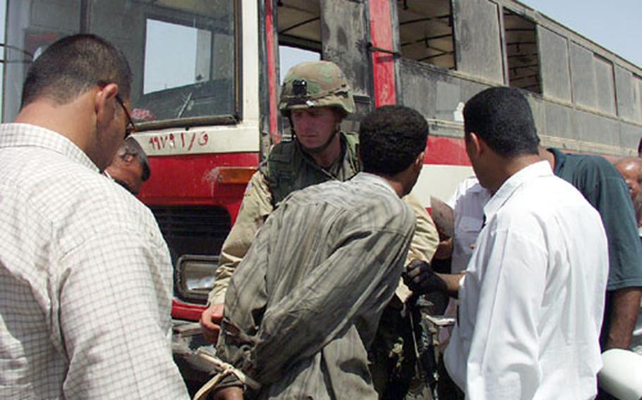 During a joint patrol with Iraqi police officers, Army Staff Sgt. Walter Vantichelt helps handcuff an Iraqi accused of stealing a city bus. The man later was released when his ownership documents proved accurate.