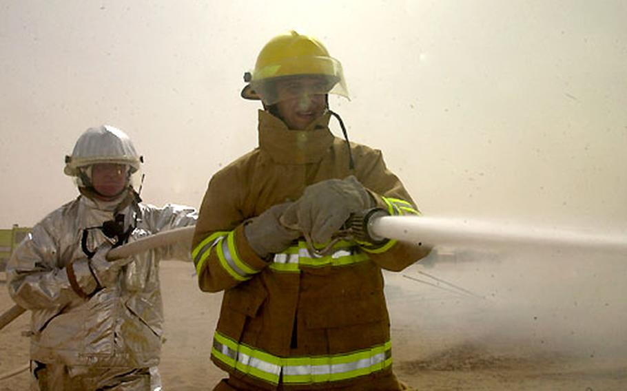 Army firefighter Staff Sgt. Patrick Hurlbert, left, and Brown & Root firefighter Slobodan Trgacevski spray the fire with water, but there was little they could do to stop the fast-moving blaze.