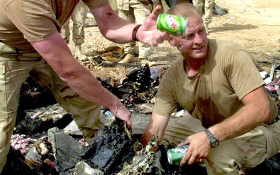 Sgt. Weston Farnsworth, left, and Staff Sgt. Kenneth Yount pass out cold sodas that survived the fire inside a melted cooler.