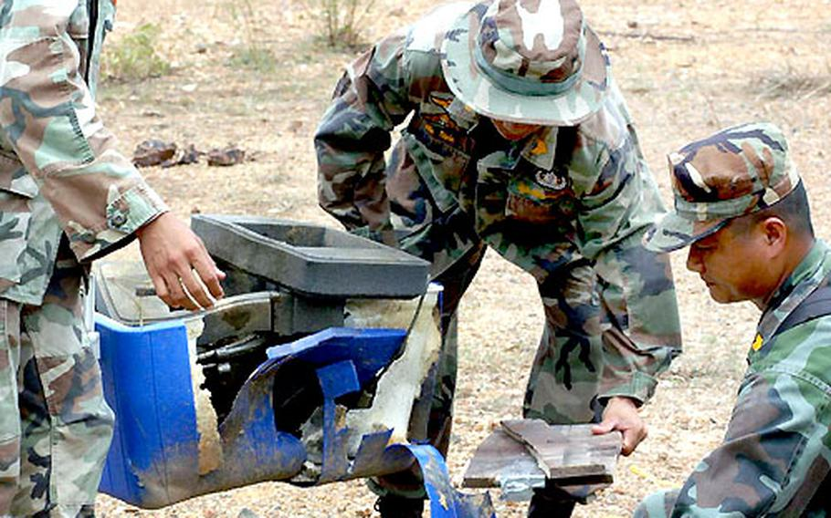 Royal Thai servicemembers pick up the remains of objects blown up as part of the demonstration Saturday.