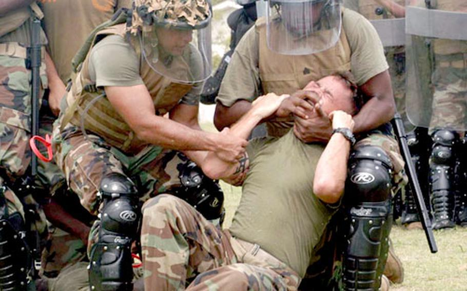 U.S. Marines and their Thai counterparts subdue a rioter as part of nonlethal-control training Monday during the annual Cobra Gold exercise in Thailand.