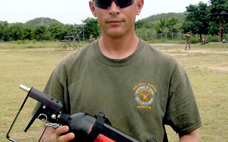Non-lethal weapons trainer Gunnery Sgt. Kenneth Kurre shows a canister of pepper spray used for crowd control.
