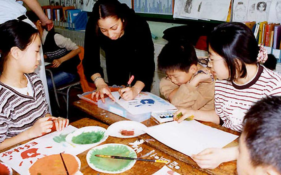U.S. Army Sgt. Koren Chavis teaches children at Seoul's Itaewon Elementary School as part of the Virtues Development Project.