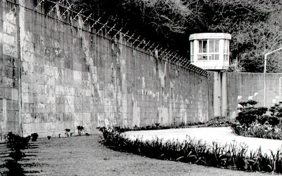 A large wall topped with barbed wire surrounds the prison in Yokosuka, Japan. The 18 U.S. servicemembers at the prison, and other qualified foreign prisoners, can petition to serve the remainder of their sentences in prisons in their home countries.