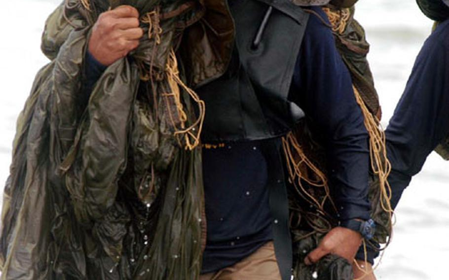 A Royal Thai Navy explosive ordnance disposal team member carries a static-line parachute from the sea off Thailand on Wednesday after a combined U.S.-Thai training jump during Cobra Gold.