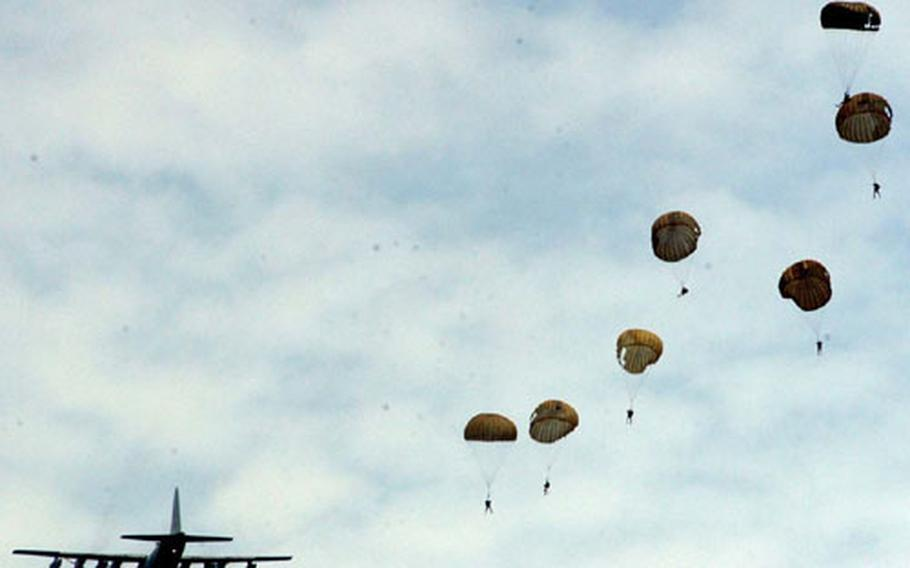 U.S. and Royal Thai Navy explosive ordnance disposal team members parachute Wednesday from a C-130 plane into the sea off Thailand during a combined U.S.-Thai training jump during Cobra Gold.