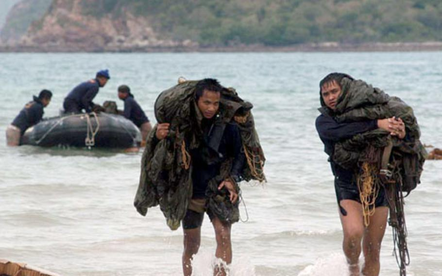 Royal Thai Navy explosive ordnance disposal team members leave a Zodiac combat rubber raiding craft for shore carrying parachutes Wednesday after jumping with U.S. Navy EOD personnel during a combined U.S.-Thai training jump during Cobra Gold in Thailand.