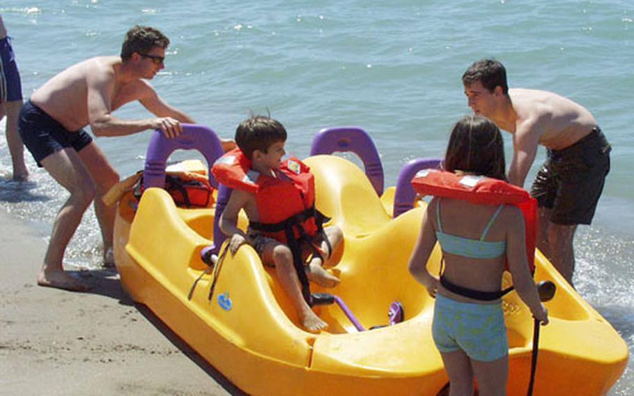 Maj. John Roney, left, helps his nephews and niece launch a four-person pedal boat Friday at the opening of the American Beach in Tirrenia, Italy. The summer got off to a fine start under a cloudless blue sky.