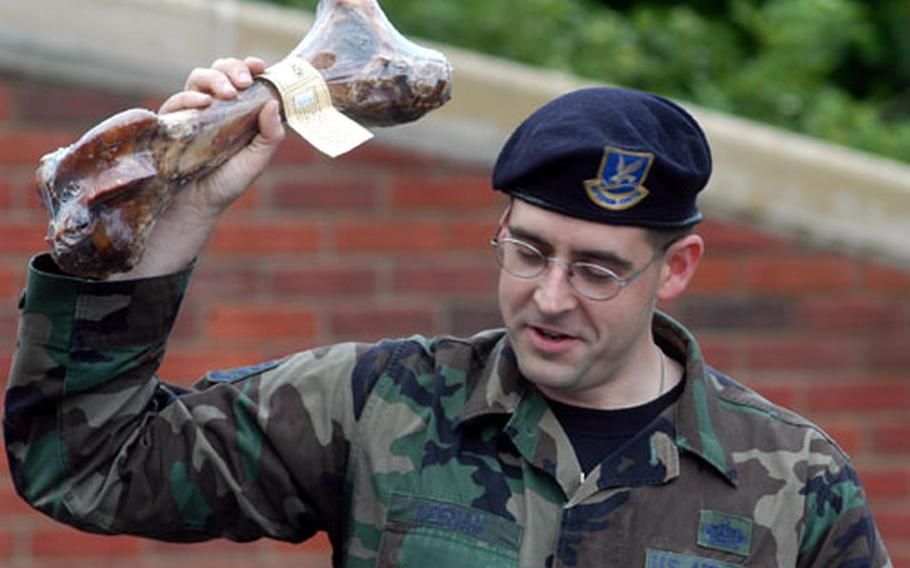 Staff Sgt. Edward Keenan holds aloft a bone given to Harras, a military working dog, who was retired from service in a ceremony Friday at RAF Lakenheath, England. Keenan, a member of the 48th Security Forces Squadaron, was master of ceremonies for the event.