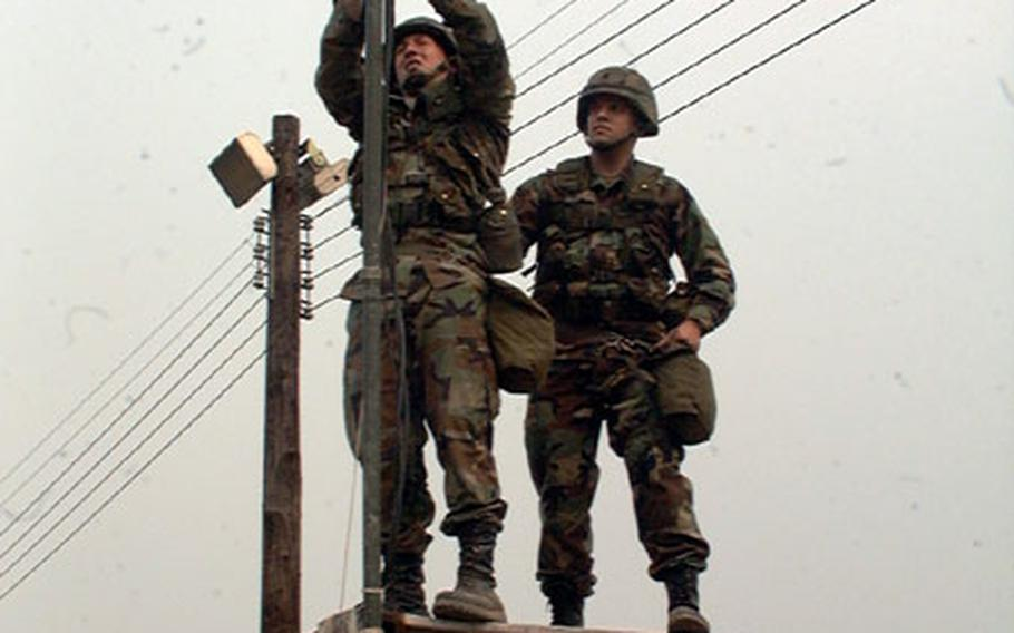 Members of Army communications unit in South Korea work on cable during unit training exercise at Army's Camp Walker in Taegu. Pfc. Jonathan Glover (left) and Spc. Dennis McVey (right) are members of Company B, 307th Signal Battalion, out of Camp Carroll in Waegwan.