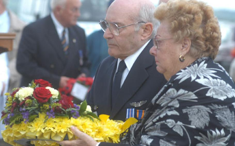 Bill Lyons, president of the 355th Fighter Group Association, and Theresa Angileri, sister of a pilot who died while with the unit in World War II, prepare to lay a wreath during a service Saturday at the unit's wartiime base in Steeple Morden, England.
