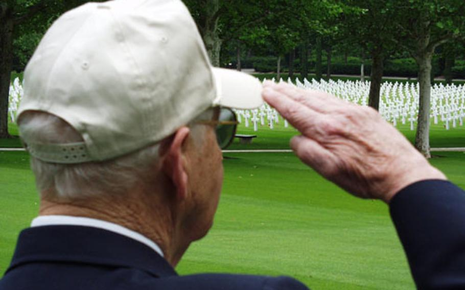 Peter Austin, a World War II veteran, salutes the flag during the playing of the national anthem at a Memorial Day Service at the Florence American Military Cemetery in Italy. Crosses marking the burial spots of thousands of his former comrades are in the background.