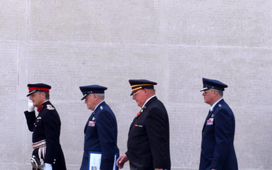 The official party arrives Monday for the Memorial Day ceremony at the Cambridge American Cemetery in Madingly, England. They pass the Wall of the Missing, which holds more than 5,000 names of missing U.S. servicemembers from World War II.