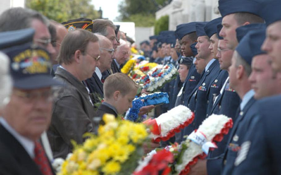 Active-duty servicemembers, right, hand wreaths to representatives of 119 organizations that placed wreaths at the Cambridge American Cemetery during a Memorial Day ceremony Monday.