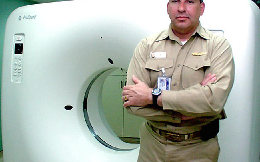 Navy Cmdr. Brian Lewis, division officer for the USNS Comfort's casualty receiving department, stands in front of the ship's CT scanner. Lewis said the scanner was critical for doctors and nurses treating casualties from the war in Iraq, and operated almost around the clock at the height of the conflict.