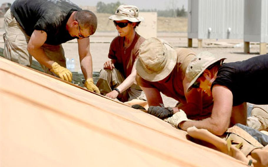 From left, Master Sgt. Rich Adkins, Lt. Col. Tracey Walker, Tech. Sgt. Richard Toumberlin and Master Sgt. Michael Schmidt stretch the canvas of a tent they are building at Kirkuk airfield, Iraq.