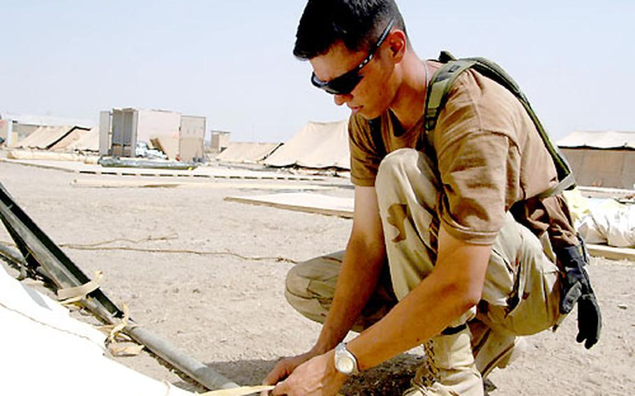 Airman 1st Class Darrel Dabeck ties down the side of a tent at Kirkuk airfield.