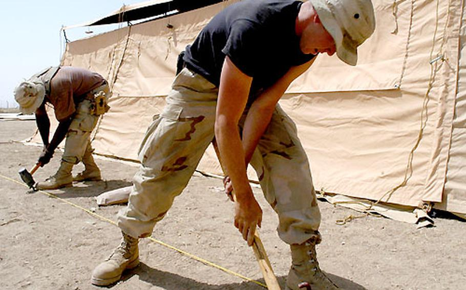 Airman 1st Class Tadd Wallace, right, and Master Sgt. Marshall Townsend hammer in stakes to support a tent they erected at Kirkuk airfield in Iraq. Members of the 506th Expeditionary Civil Engineering Squadron from McConnell Air Force Base in Wichita, Kan., and volunteers from other Air Force units stationed at the airfield are building a tent city with 194 billeting tents.