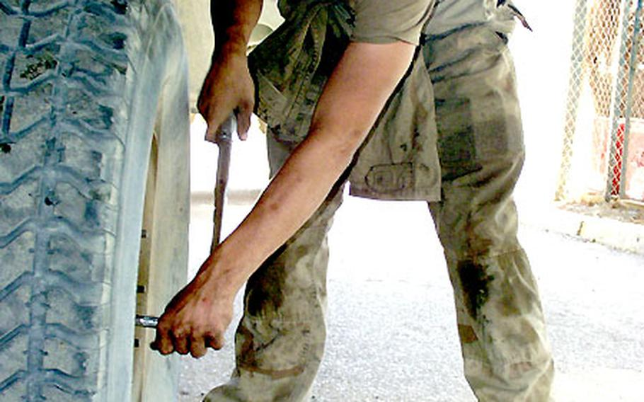 Pfc. Ross Scarbrough tightens the lug nuts on a Humvee wheel. Scarbrough and mechanics at V Corps' Special Troops Battalion kept 800 vehicles in top shape during the Iraq war.