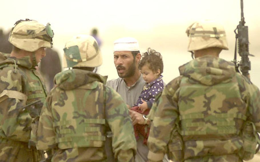 An Iraqi man tries to convince troops from the 1st Battalion, 15th Infantry Regiment to let him pass through a checkpoint near the city of As Samawah on March 26.