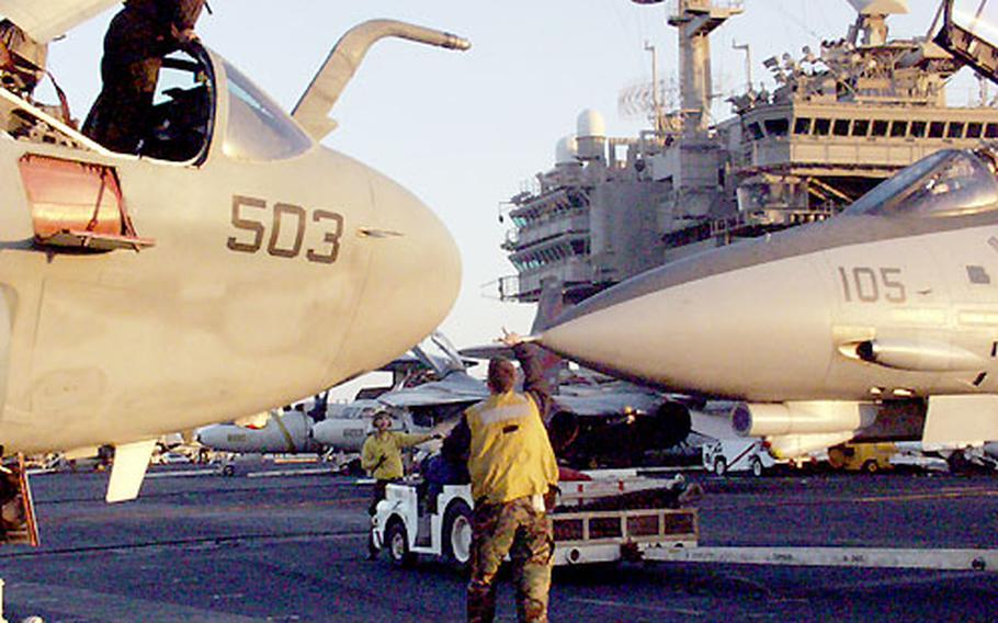 A sailor in an EA-6B Prowler, left, looks down at a fighter getting close to the aircraft while it's being parked on the USS Kitty Hawk flight deck.