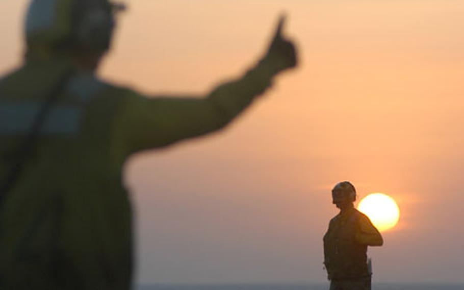 Sailors work on the flight deck of the USS Kitty Hawk during sunset as a jet flies overhead.