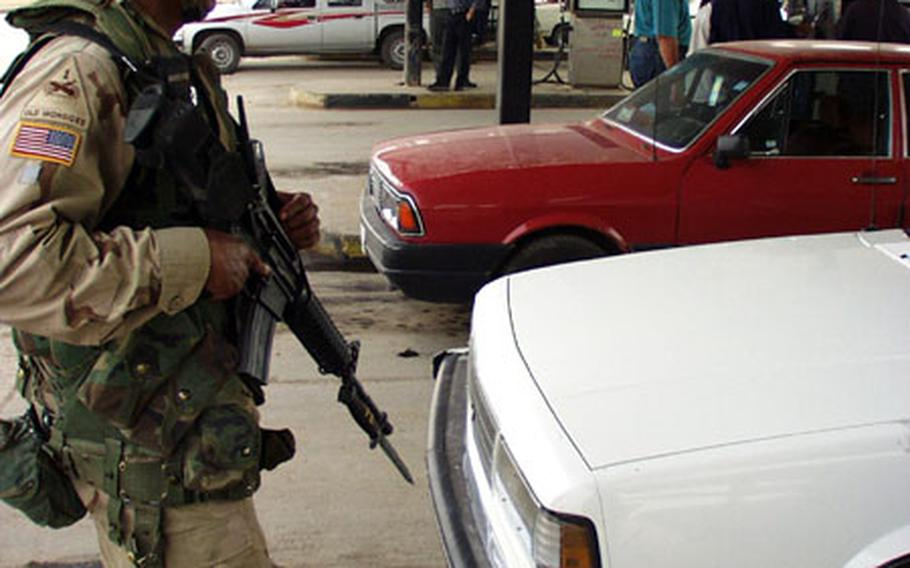 Sgt. 1st Class Joseph Hadley, guarding a gas station in Baghdad, Iraq, has found a new use for the bayonette on his weapon: He punches holes in plastic jerry cans used by black marketers.