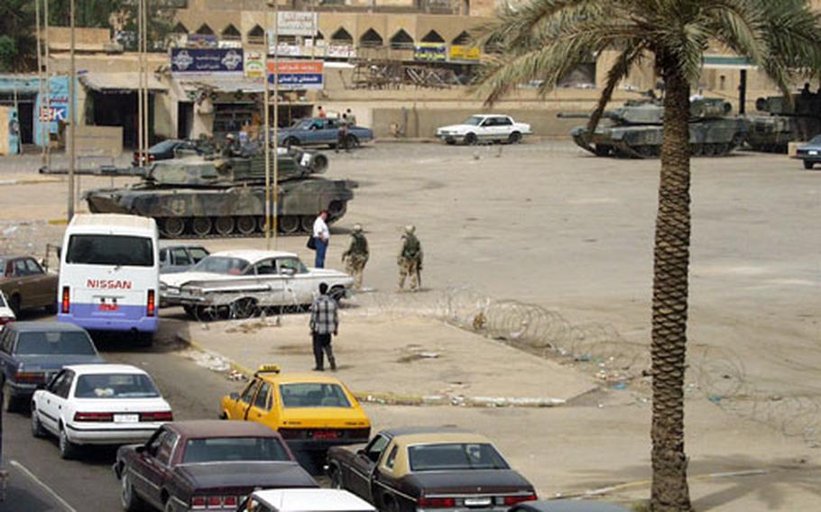 Three M1-A1 tanks and a platoon of 1st Armored Division soldiers guard a gas station in the Mansur district of Baghdad as drivers queue up to fill up.