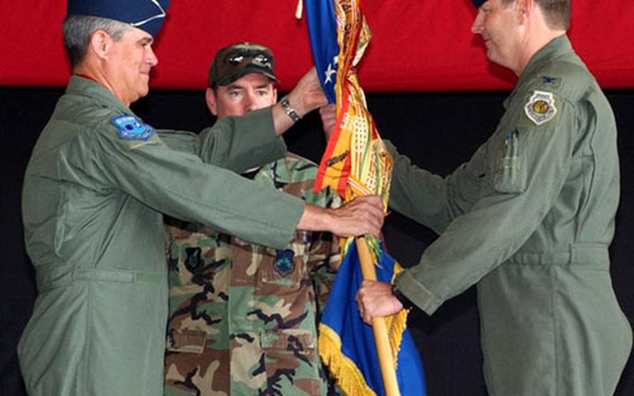 Lt. Gen. Lance Smith, left, 7th Air Force Commander, passes the 8th Fighter Wing guidon to the 42nd Wolf Pack wing commander, Col. Robin Rand.