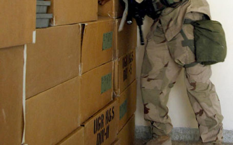 Spc. Luis Jau, of the 10th Mountain Division's 2nd Battalion, 14th Infantry Regiment from Fort Drum, N.Y., stacks the last box of food in a room at the Khatuzeen Center for Social Action in Irbil, Iraq.