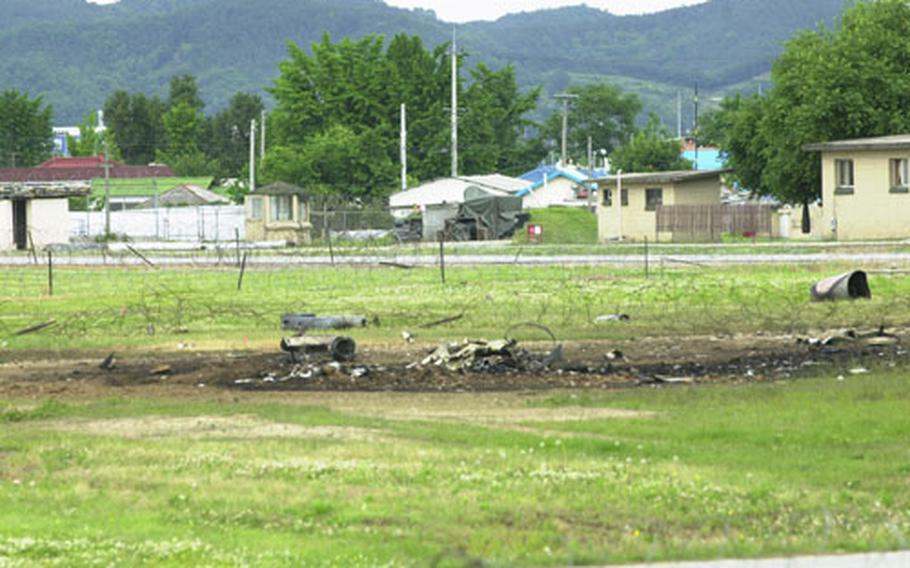 A charred field and small parts are all that remain from an F-16 that crashed just off the runway Thursday night at Osan Air Base.