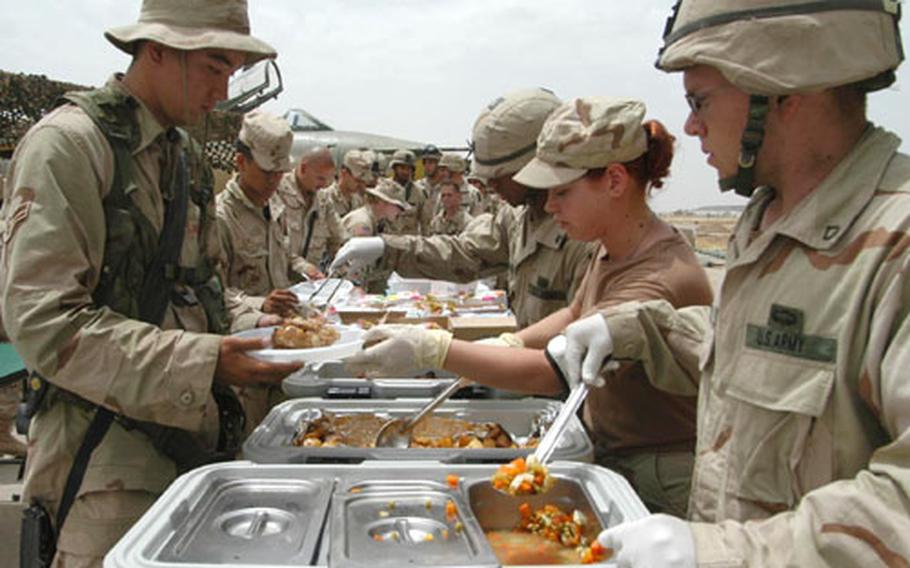 Pfc. Ty Starkey, right, of the 173rd Airborne Brigade, Airman 1st Class Dana Stanford of the 506th Expeditionary Services Squadron, and Sgt. Carlos Ramos of the 173rd serve up chicken, potatoes and vegetables to soldiers and airmen at the belated Memorial Day picnic at Kirkuk airfield, Iraq. 4000 servings were prepared for the day's feast.