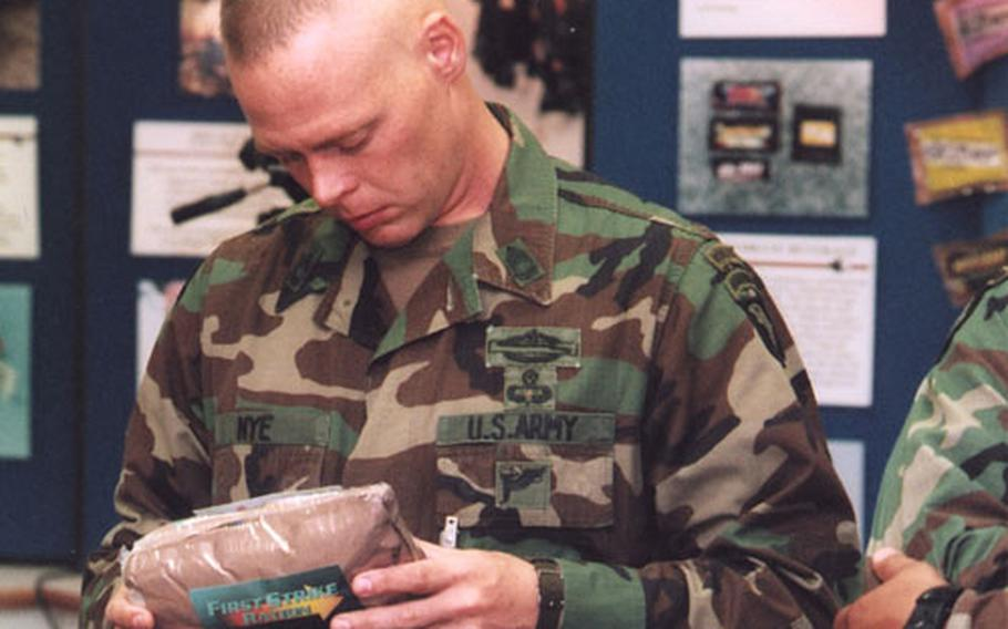 SFC Charles Nye from 1st Battalion, 187th Infantry, Fort Campbell, holding one of the new MRE packs, during a Sept. 5, 2002, visit to the DOD Combat Feeding Directorate ration display room at the US Army Soldier Systems Center.