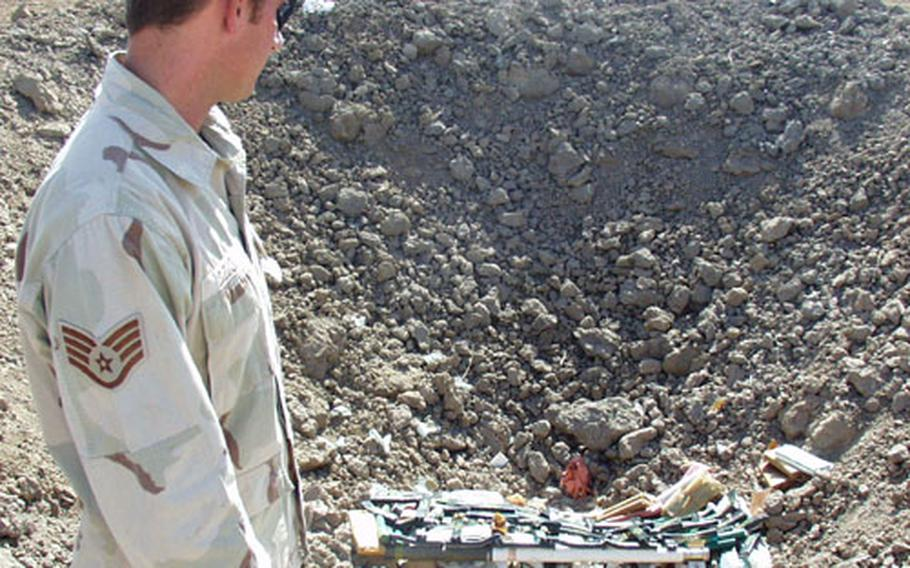 Air Force Staff Sgt. John Dziok looks at a pile of unexploded ordnance and explosives that he and other members of the Explosive Ordnance Disposal Team gathered together at Baghdad International Airport, shortly before detonating the pile.