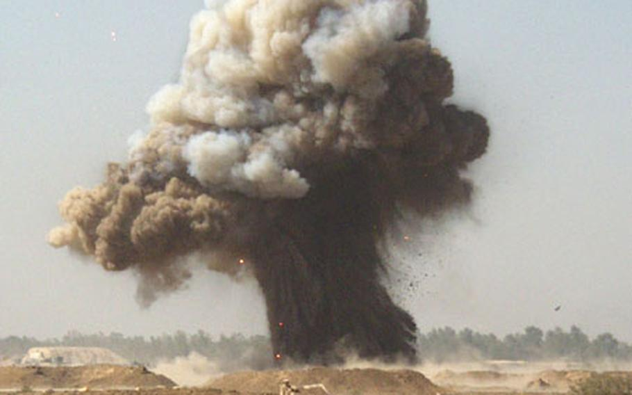 A plume of smoke marks the site where the Air Force's Explosive Ordnance Disposal team blew up a small pile of explosives at Baghdad International Airport recently.