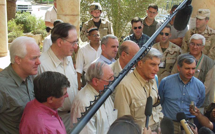 A group of nine U.S. senators, led by John Warner and Carl Levin, answer questions Tuesday during a visit to one of Saddam Hussein's former presidential palaces, now a headquarters for the Coalition Provisional Authority. The senators are all members of the Senate Armed Services Committee.