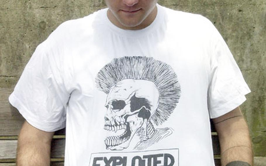 USS Essex sailor Petty Officer 3rd Class Aaron Sanders shows the black and white drawing on his T-shirt at Sasebo Naval Base, Japan. Some T-shirts with offensive language and symbols are prohibited by the Navy civilian attire regulations.
