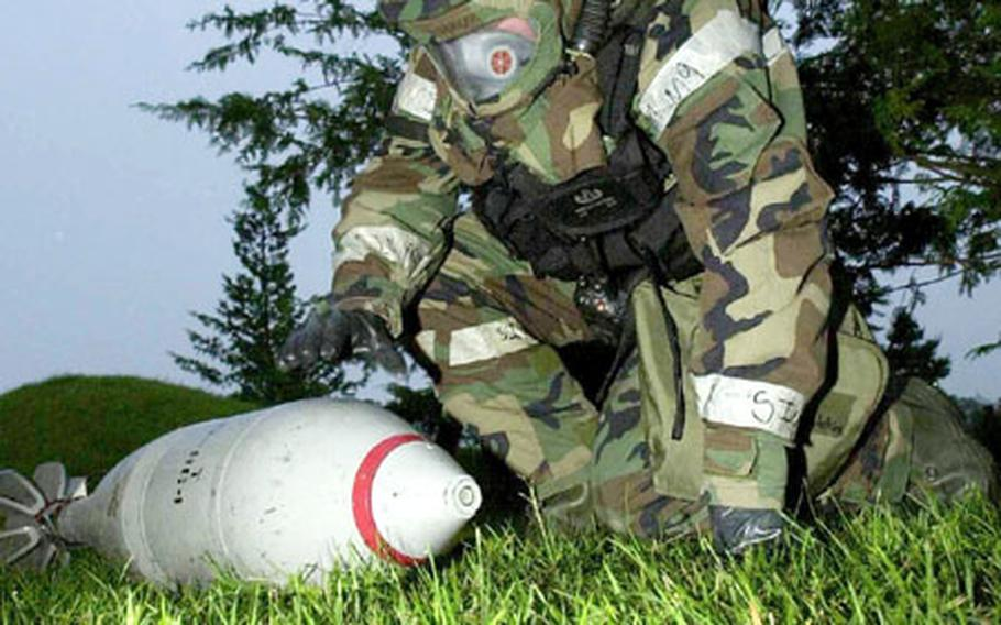 Senior Amn. Kimberly Hutchens marks a simulated 240mm mortar that failed to explode near the command post. During the exercise, explosive ordnance disposal specialists like Hutchens practiced disarming unexploded ordnance, or UXOs, like the mortar.