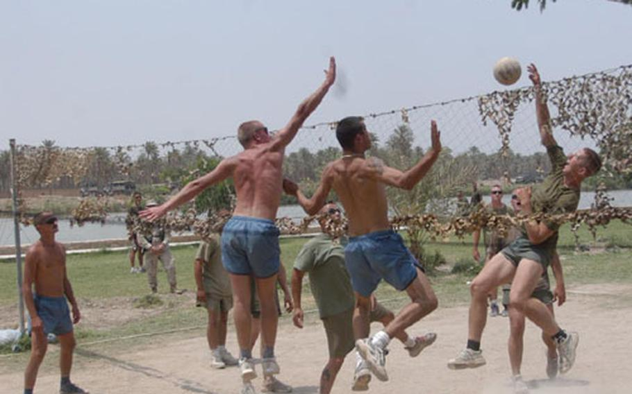 U.S. Marines, on the right side of the net, play against Polish forces during a Fourth of July volleyball tournament at Camp Babylon in Hillah, Iraq. The game was played along the Euphrates.