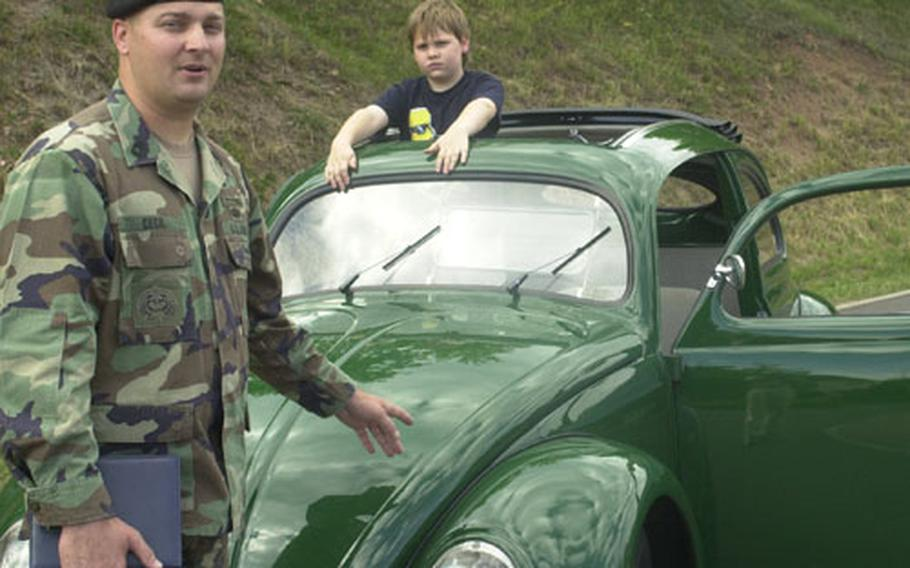 Master Sgt. Joseph Cecil doing what he likes to do most — talk about his 1952 Volkswagen Beetle. Cecil says whenever he drives the car, locals wave, smile and stop to talk about their memories of Germany's ubiquitous Peoples' Car. His son, Benjamin, checks out the sunroof. (enw# 61p cs)