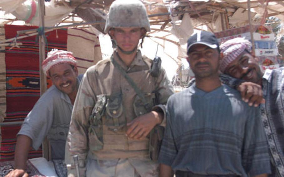 Pfc. Jonnie Seely, with Company B, 1st Battalion, 7th Marines, stands with vendors at the market outside Camp Babylon near Hillah, Iraq. Seely patrols the market for infractions, fake goods and disputes.
