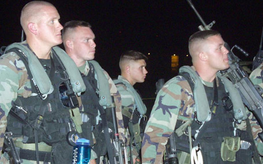 U.S. Marines from Marine Corps Security Force Company Europe at Naval Station Rota, Spain, wait to board a C-130 transport plane for Liberia early Monday morning. The Marines are providing security for a 15-member U.S. military survey team that will assess the requirements for a possible humanitarian assistance mission.