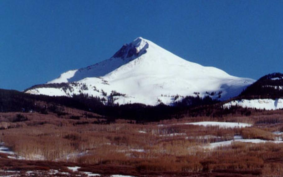 """Lone Cone Mountain in early spring, before the snow runoff. A rare day of azure at """"The Cone."""" Usually the sky is a washed out, pale blue. Local ranch owners Ron and Ruby Clements are offering a free vacation to servicemembers returning from Iraq."""