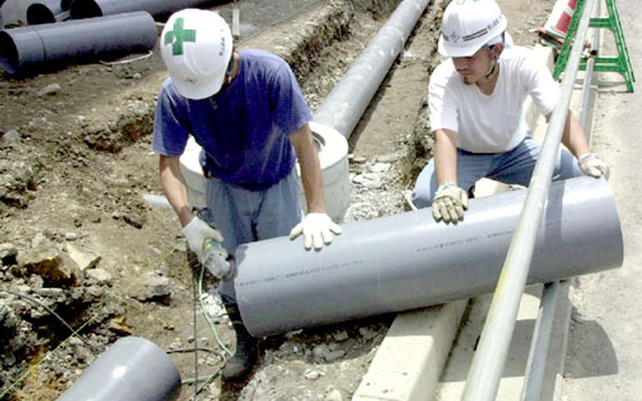 Construction workers trim a length of PVC pipe for Sasebo's new Bachelor Officer's Housing complex.