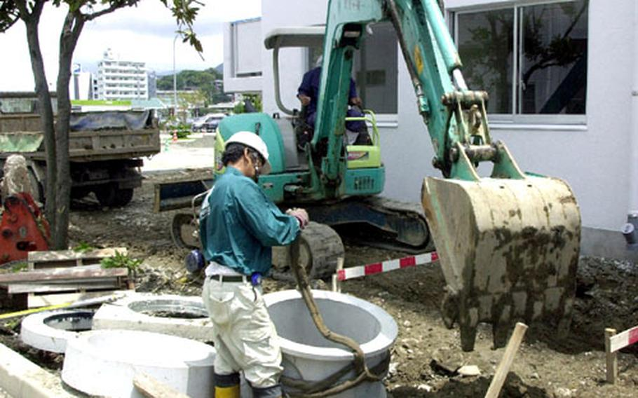 """A Japanese contractor attaches a """"lifting sling"""" to a piece of drain piping at Sasebo's new Bachelor Officer Housing complex."""