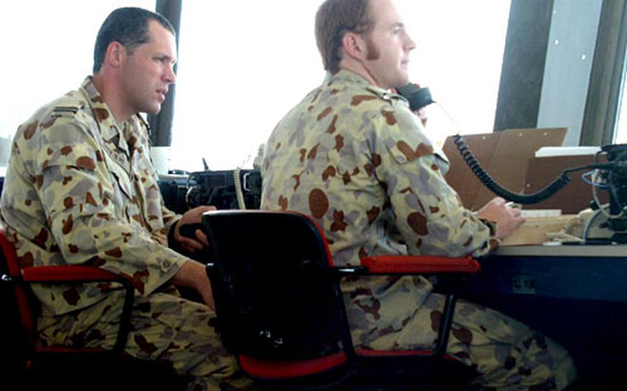 Flight Lt. Michael Duyvene De Wit, left, and Flight Officer Andrew Chapman converse with an aircraft from the air control tower at Baghdad International Airport.