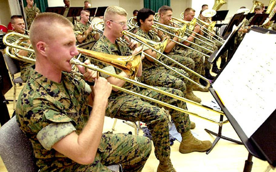 Marine Cpl. Andrew Toothman belts out tunes on his trombone during rehearsals for the 3rd MEF Band's Annual Summer Concert.