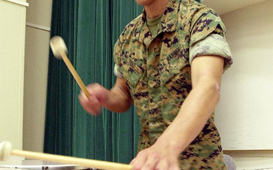 Marine Cpl. Jeffrey Higgs keeps time on the kettle drums during a rehearsal.