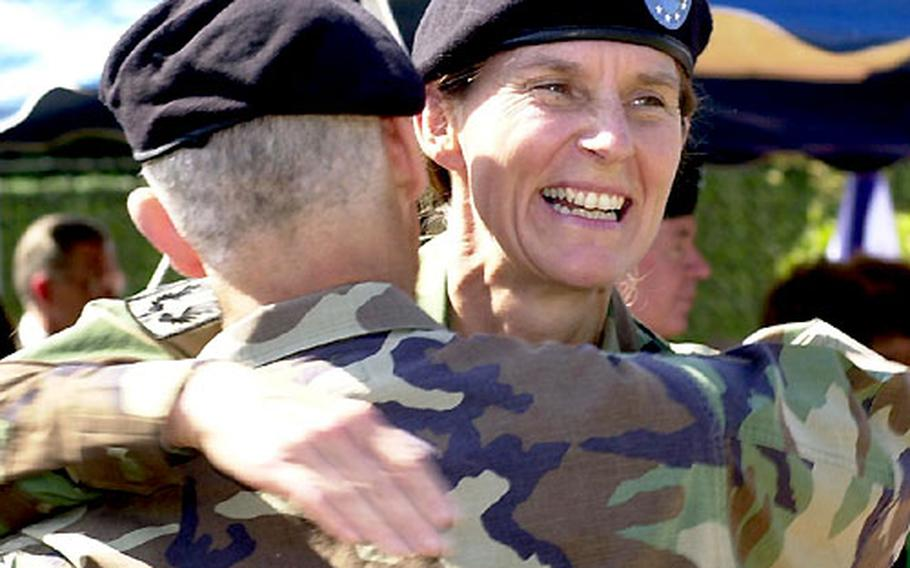 Col. Rhonda Cornum, right, gets a congratulatory hug from outgoing commander Col. David Rubenstein on Friday after assuming command of the Landstuhl Regional Medical Center.